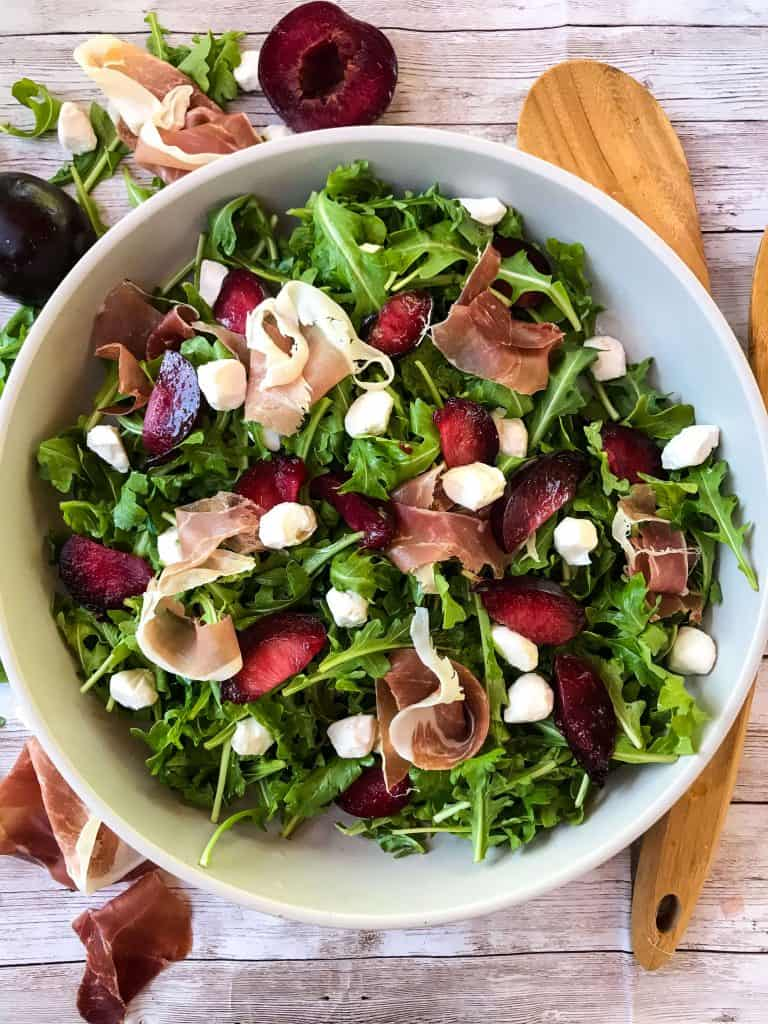 Prosciutto Plum Arugula Salad with Mozzarella in a bowl on light wood