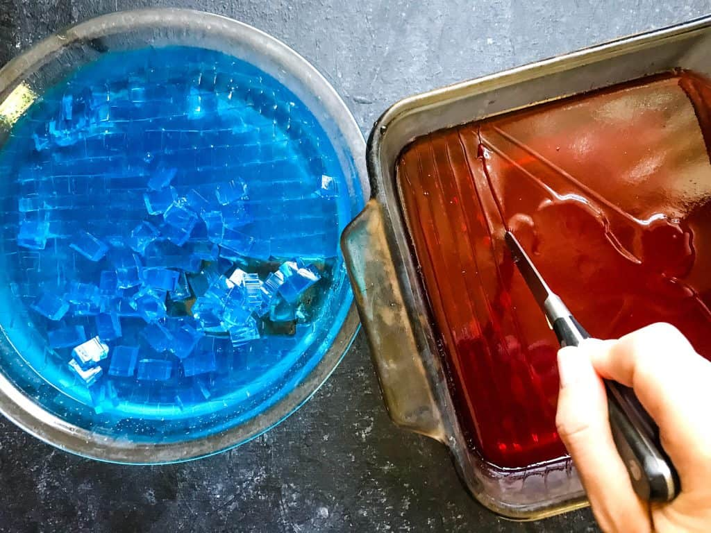 Cutting red and blue jello into cubes