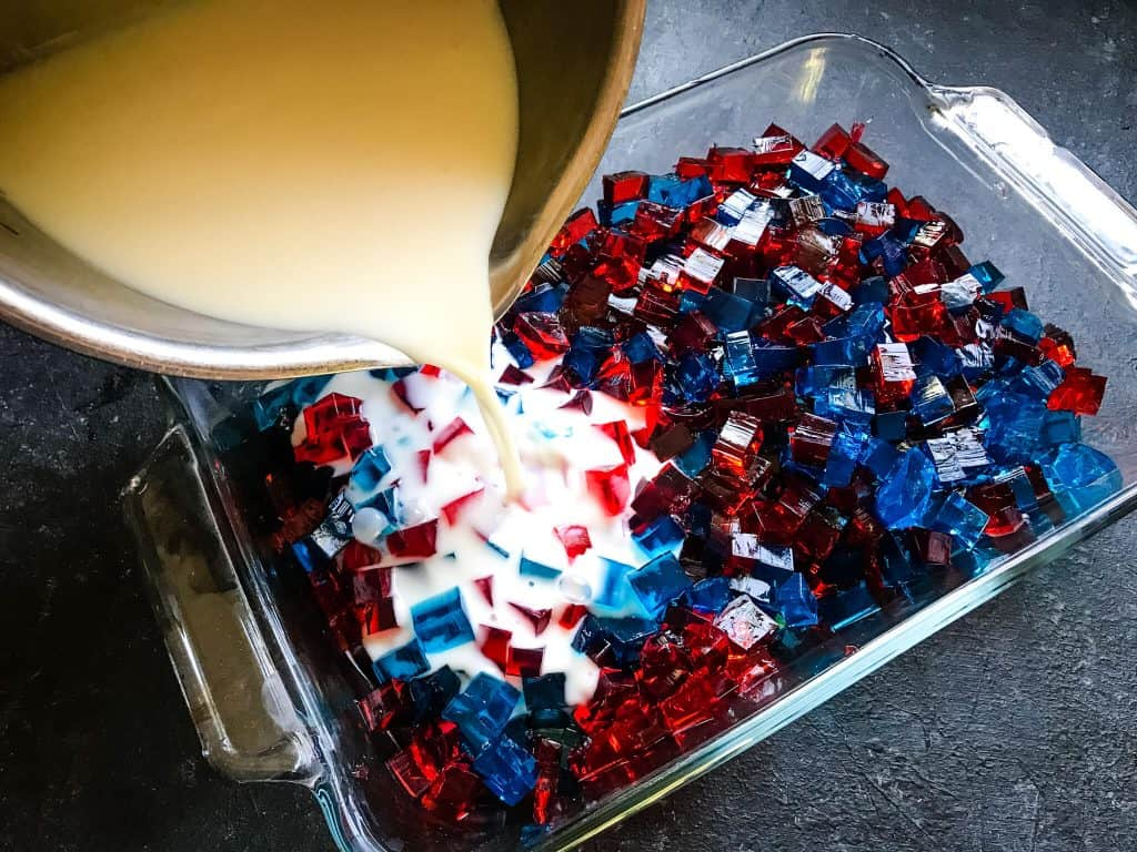 Pouring white gelatin into red and blue cubes inside a baking dish