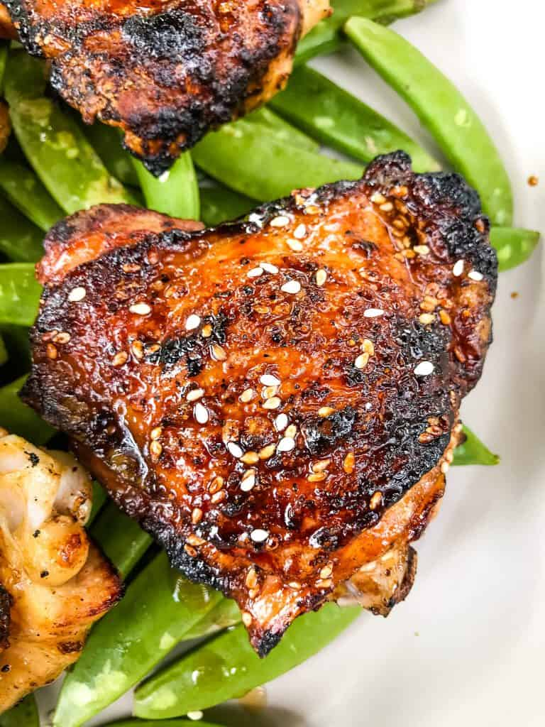 Sesame Soy Glazed Grilled Chicken Thighs are an easy grilled chicken recipe. BBQ bone in grilled chicken thighs are coated in a simple Asian glaze sauce. #grilledchickenthighs #glazedchickenrecipes #asianchickenrecipes