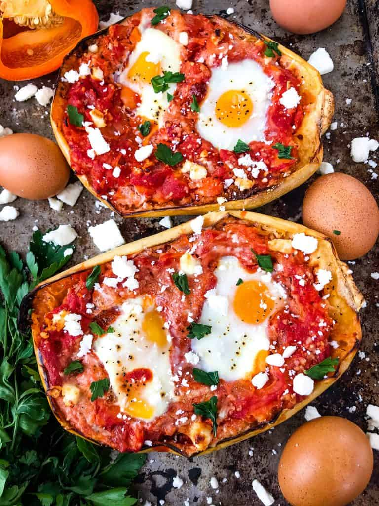Two spaghetti squash halves with red sauce, cheese, and eggs cooked in it