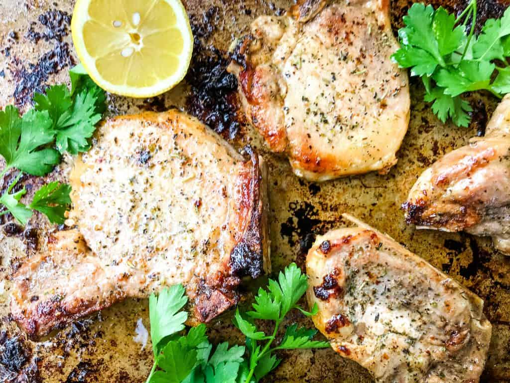 Italian Baked Pork Chops on a baking sheet with herbs