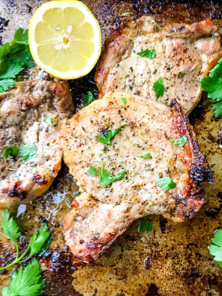 Italian Baked Pork Chops on a pan with lemon and parsley