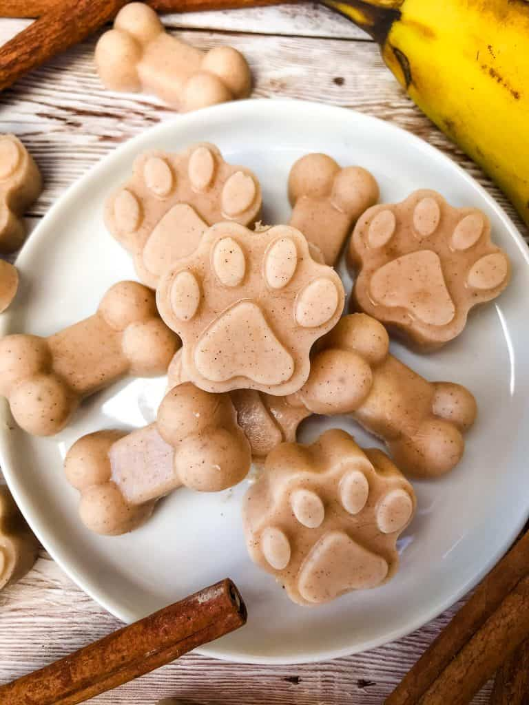 Frozen Cinnamon Banana Dog Treats on a white plate on wood surface