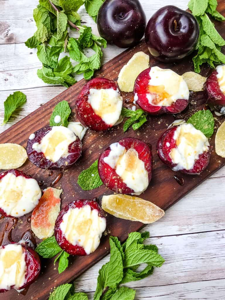 Grilled Plum Dessert with Ginger Honey Yogurt on a dark wood board surrounded by mint