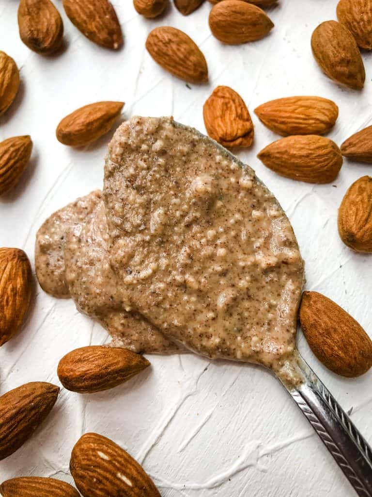 A spoon of Homemade Crunchy Almond Butter with almonds around it