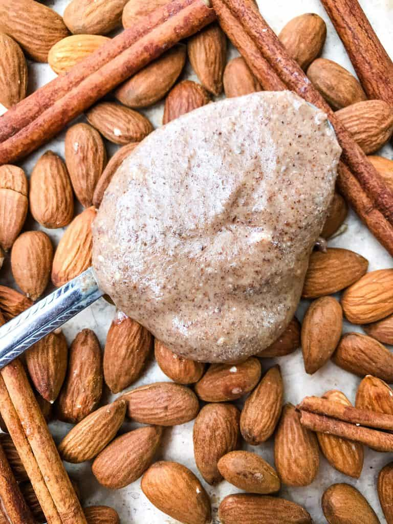 A spoon full of Homemade Cinnamon Almond Butter on top of almonds and cinnamon sticks