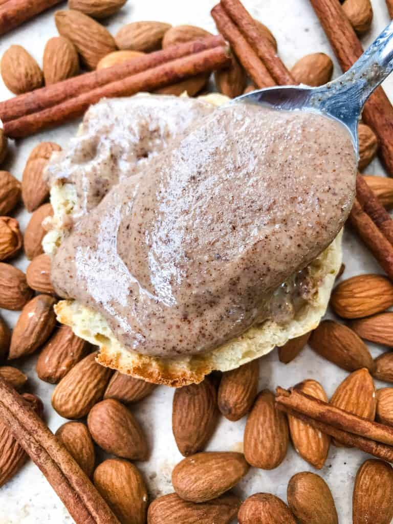 A spoon pouring nut butter on an English muffin