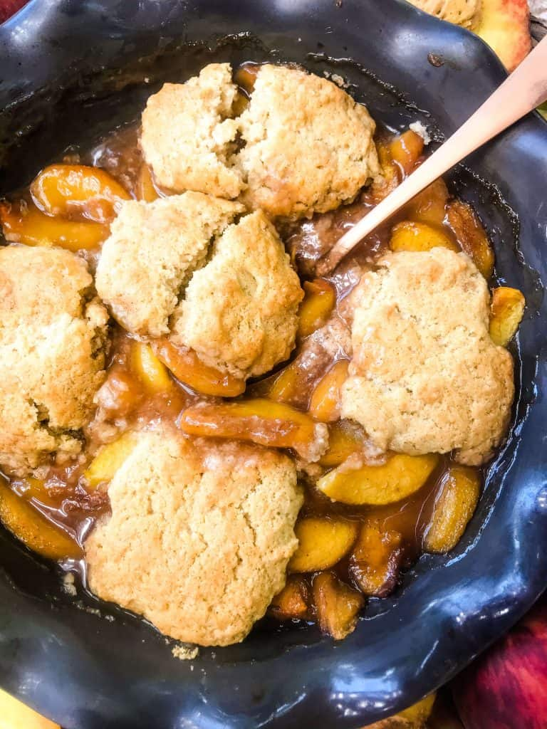 Pie dish of Easy Peach Cobbler with a spoon in it