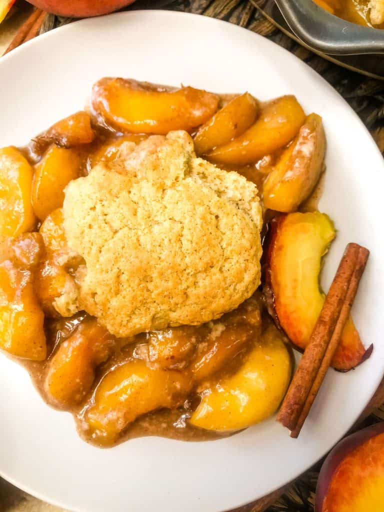 A plate of Easy Peach Cobbler with a cinnamon stick