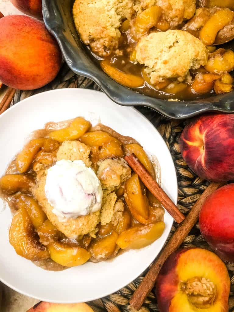 A dish of Easy Peach Cobbler with ice cream next to a cobbler dish