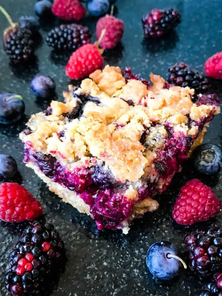 Mixed Berry Crumble Bars surrounded by berries on a black surface