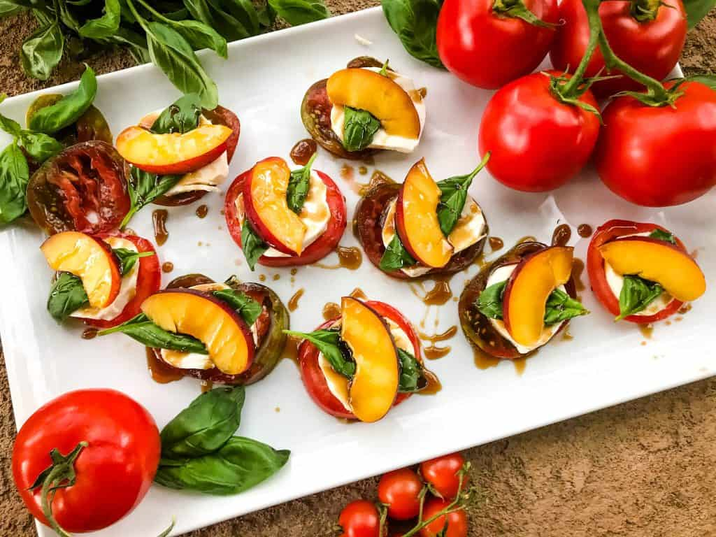 White platter of Nectarine Tomato Caprese Salad (Peach Caprese Salad) stacks with tomatoes and basil around it