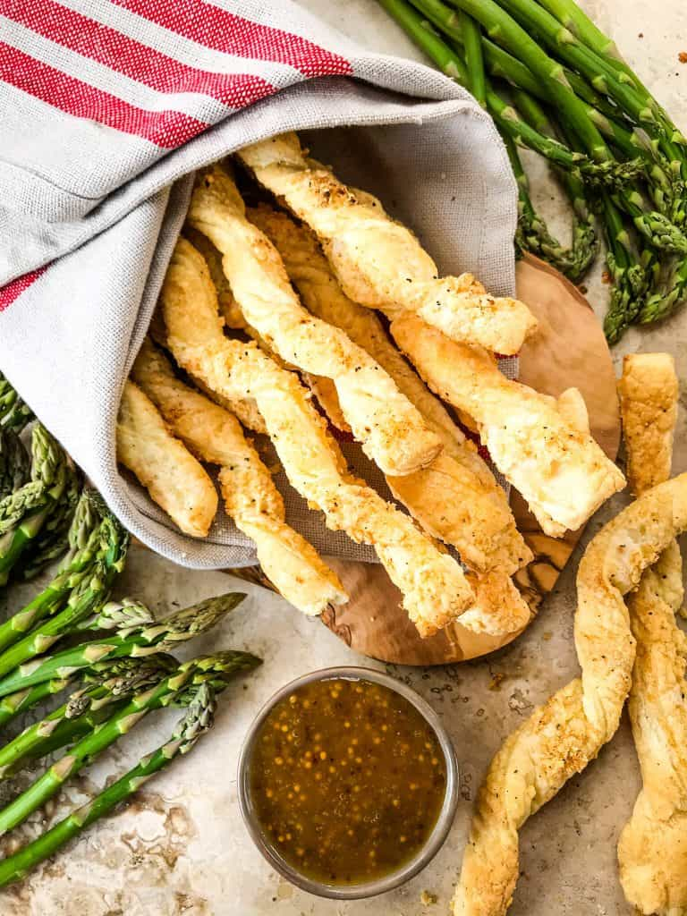 Garlic Parmesan Cheese Straws next to a bowl of honey mustard