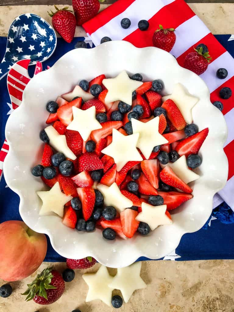 A white bowl full of strawberries, blueberries, and white star peaches