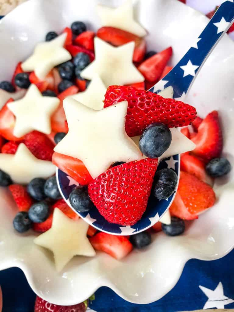 A spoon of Patriotic Red, White, and Blue Fruit Salad