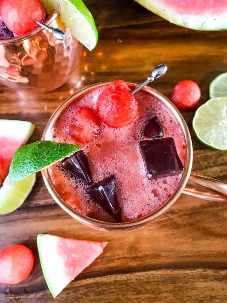 Top view of Watermelon Moscow Mule with limes, watermelon pieces, and watermelon balls around it