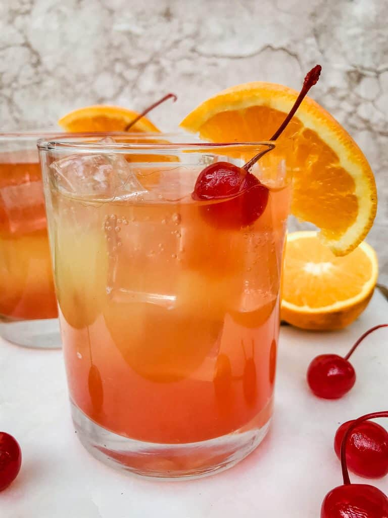 A glass of Copycat Olive Garden Venetian Sunset Champagne Cocktail with a cherry and orange slice
