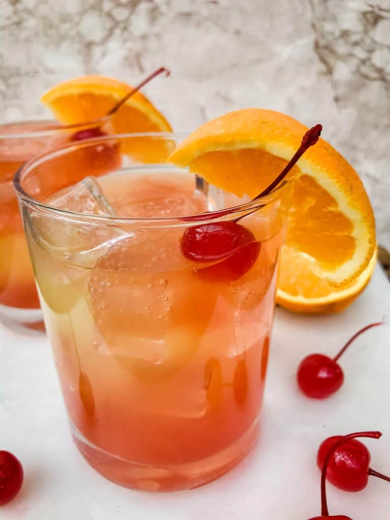 Orange, yellow, and red summer cocktail in a glass