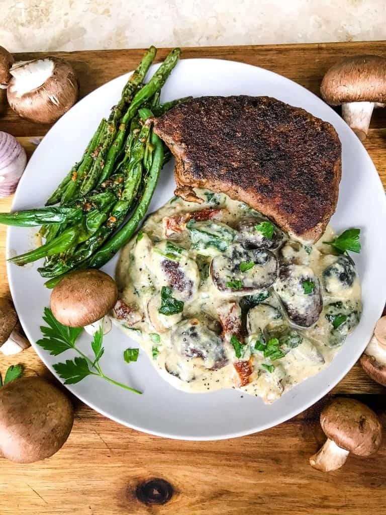 A plate with Tuscan Creamy Mushrooms, steak, and green beans