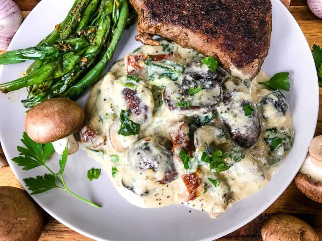 Tuscan Creamy Mushrooms with sun-dried tomatoes, spinach, and garlic in a Parmesan cream sauce