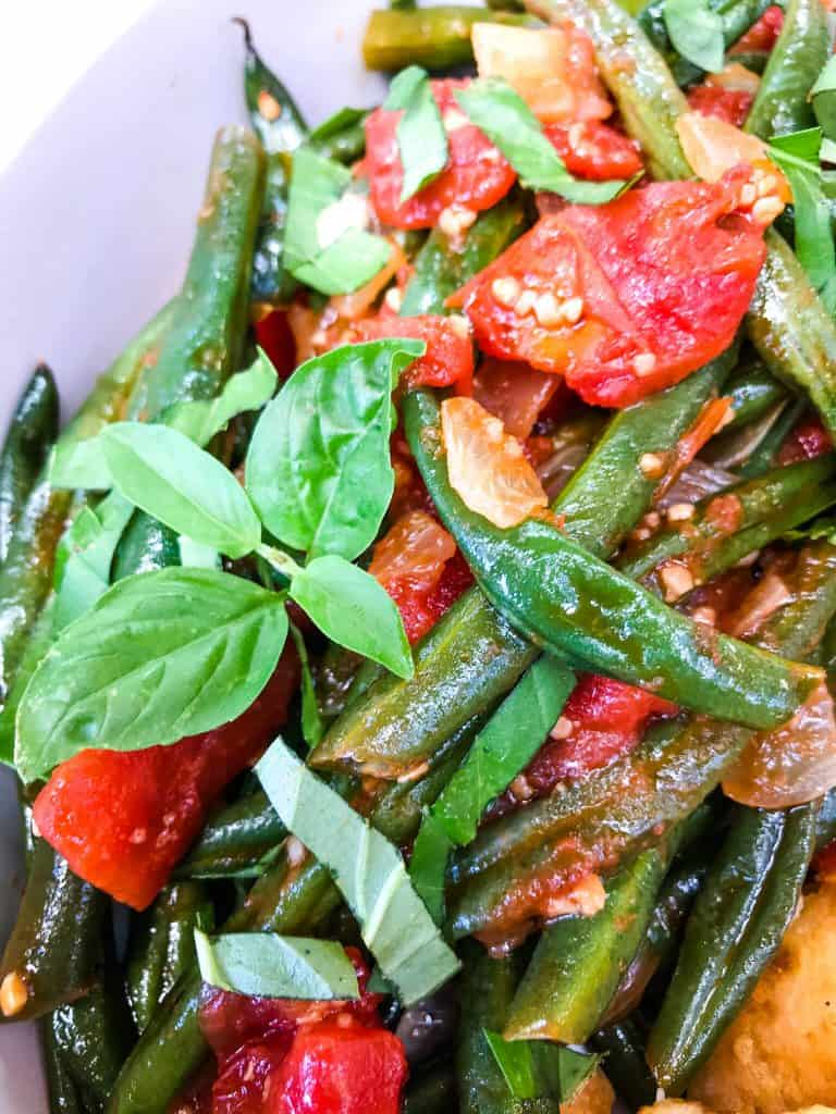 A close up of Tomato Garlic Italian Green Beans with basil leaves