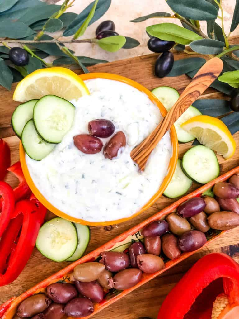 A bowl of Greek Tzatziki Yogurt Sauce with a wooden spoon surrounded by cucumber, lemon, and olives.