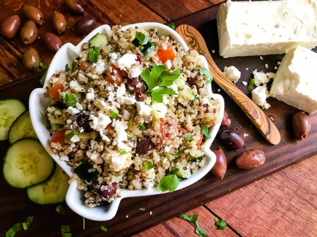 A bowl of Greek Quinoa Salad surrounded by ingredients on wood boards