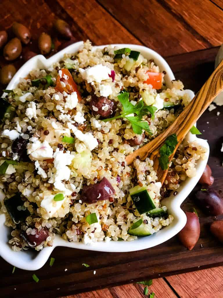 A bowl of Greek Quinoa Salad with a wood spoon