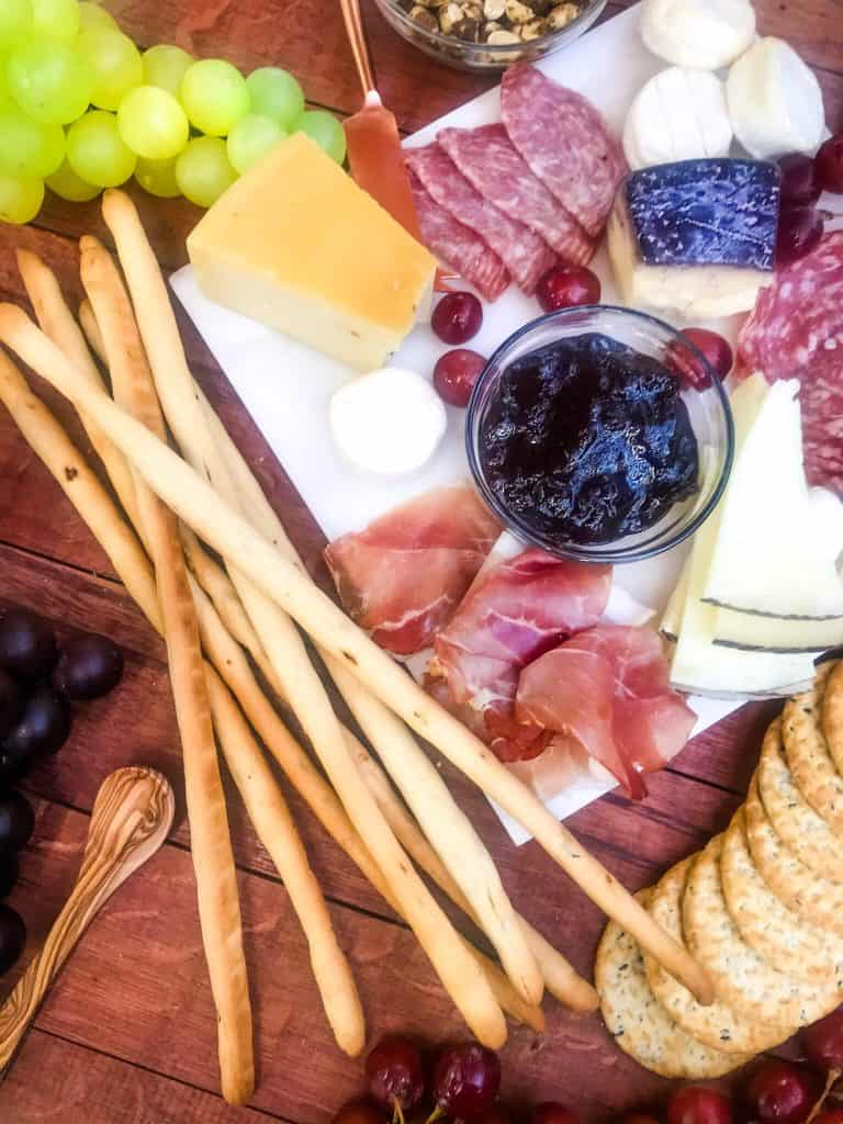 Easy Plum Jam Recipe on a charcuterie board with breadsticks
