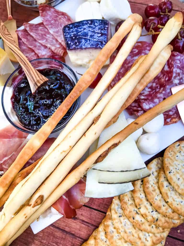 Roasted Garlic Grissini (Italian Breadsticks) laying across a charcuterie board