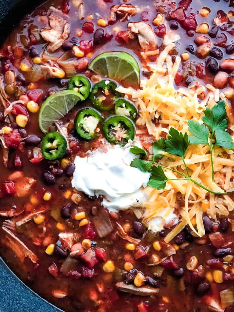 A close up of Chicken Taco Soup featuring beans, corn, chicken, and tomatoes.