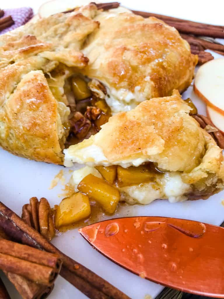 A wedge of Cinnamon Apple Baked Brie in Puff Pastry cut out of the round
