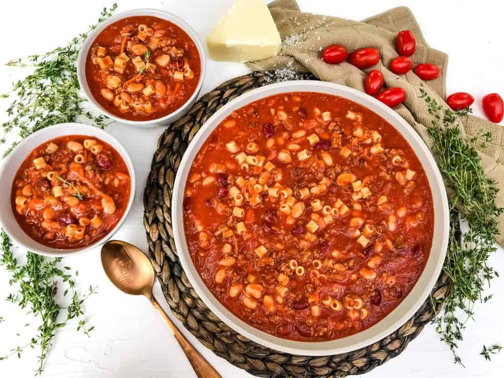 A large bowl and two serving sized bowls of Copycat Olive Garden Pasta Fagioli Soup surrounded by herbs