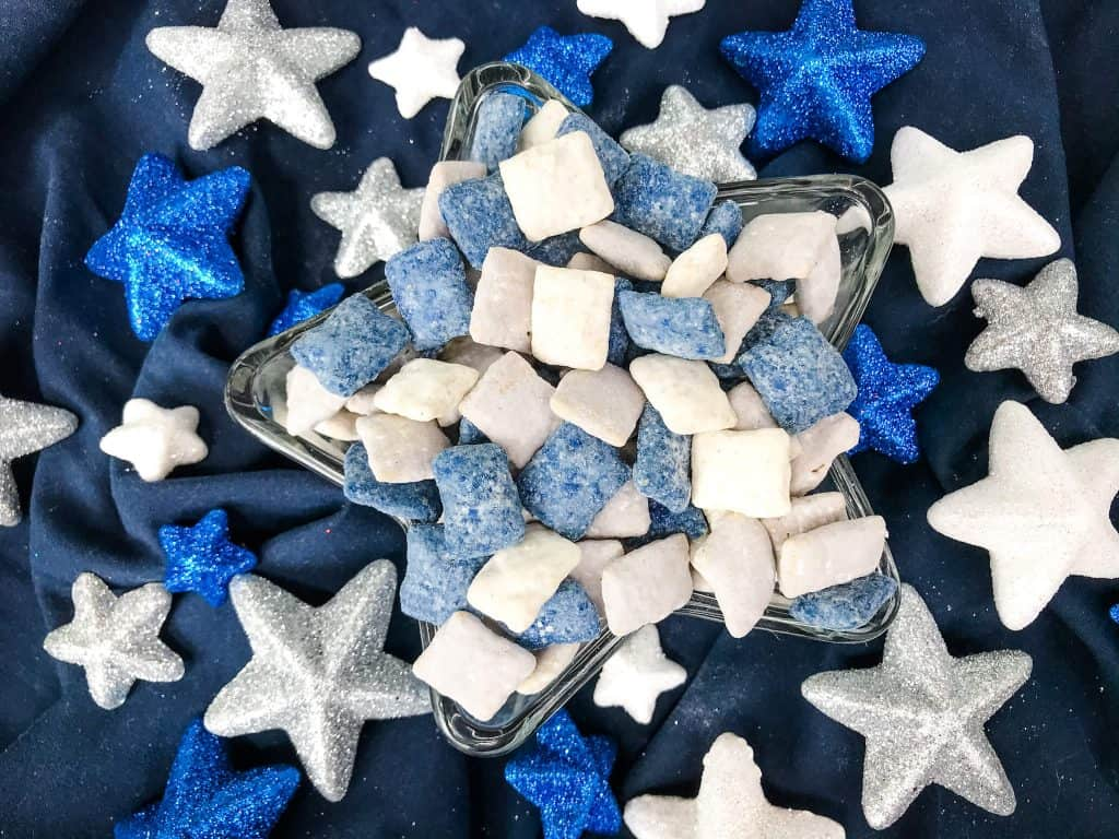 Blue, gray, and white muddy buddies in a dish surrounded by colored glitter stars