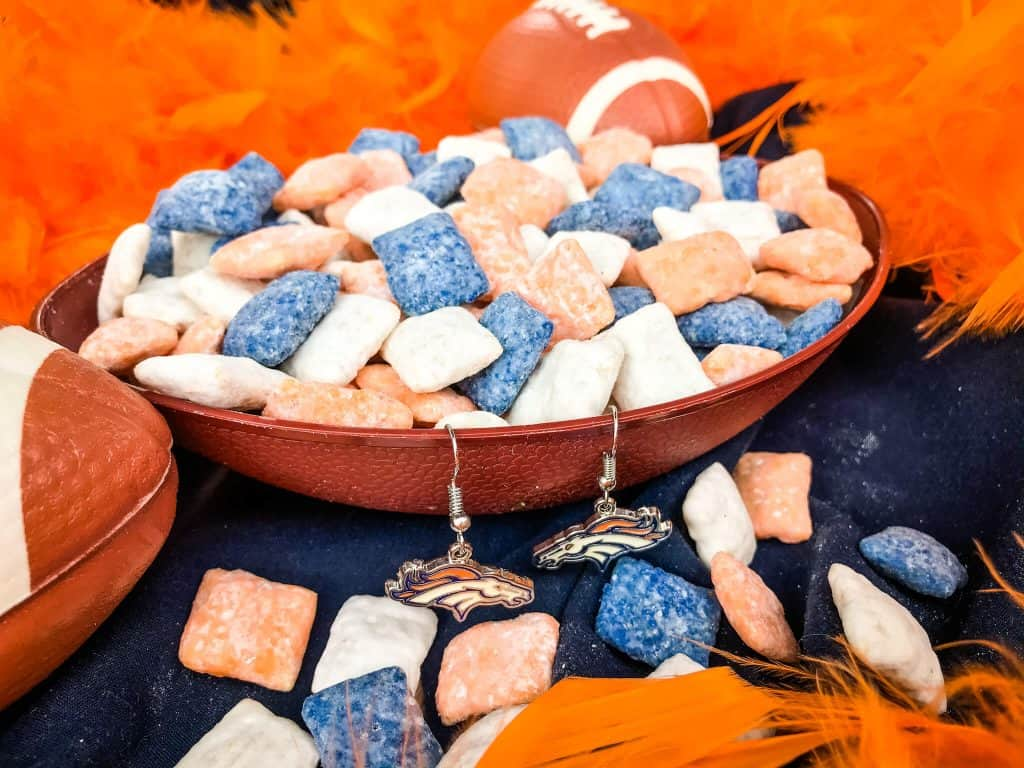 Blue, orange, and white muddy buddies in a football bowl with an orange boa