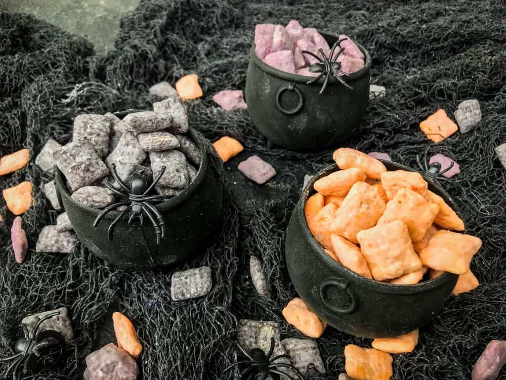 Cauldrons filled with separated orange, black, and purple Halloween Puppy Chow on a gray gauze