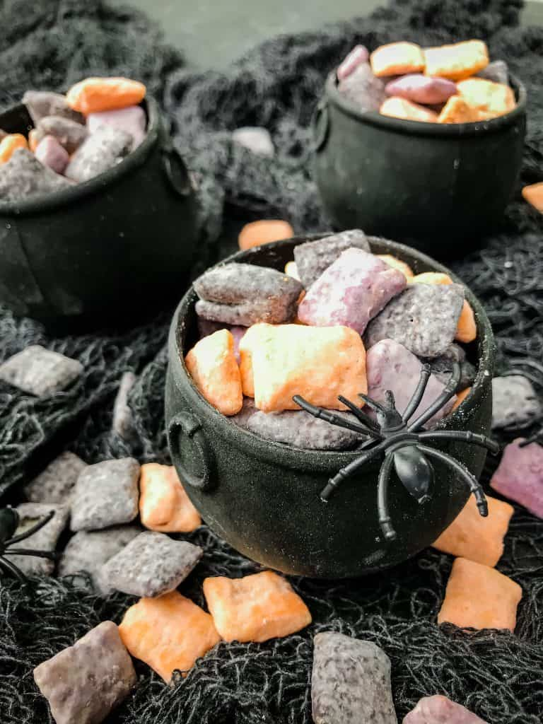 Halloween Puppy Chow in small cauldrons with a spider