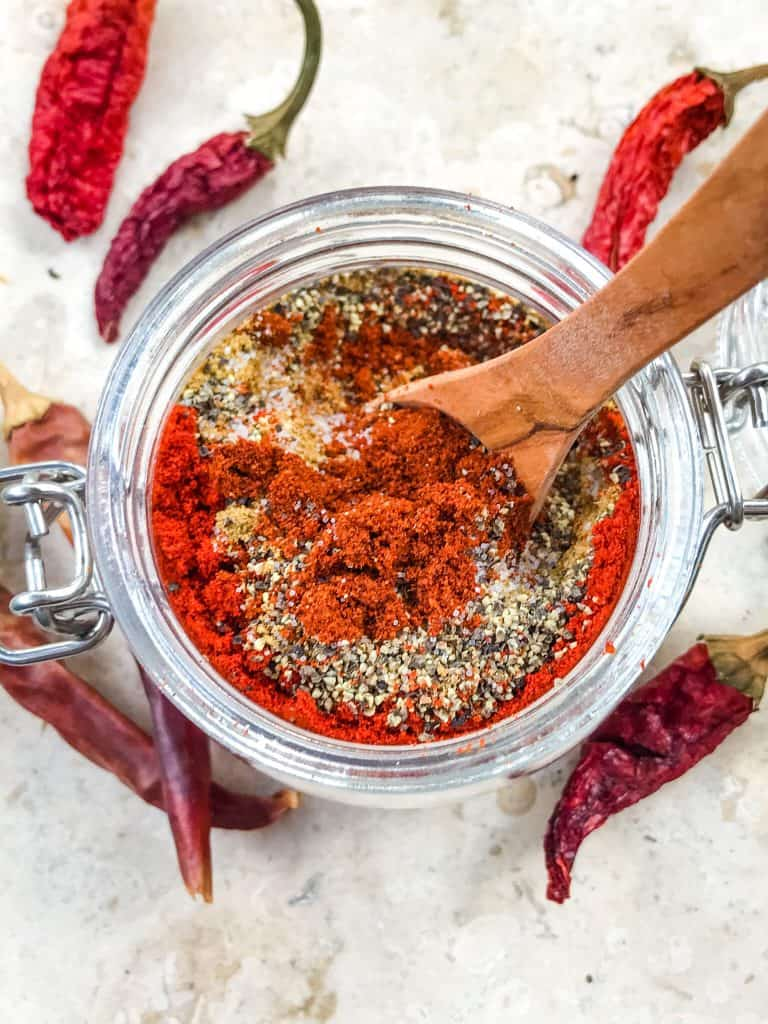 A jar from top view with layered spices for Homemade Taco Seasoning with wooden spoon