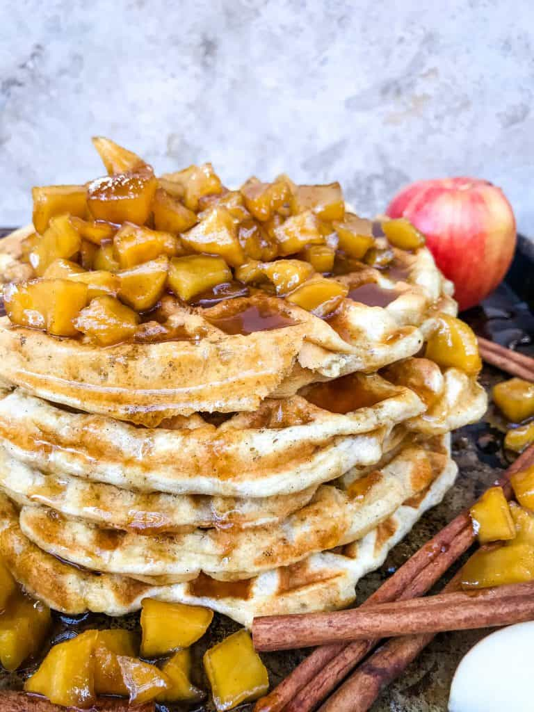 A stack of waffles with apples on top