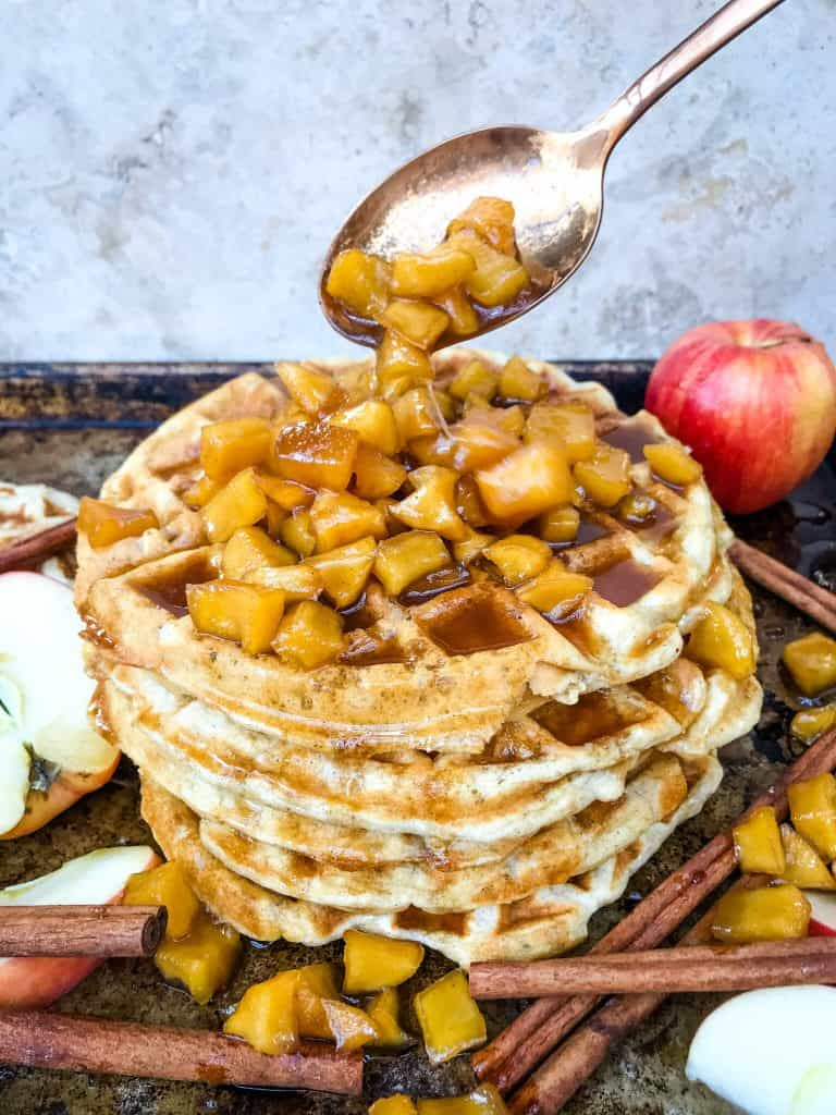 A spoon pouring cinnamon apple sauce over a waffle stack
