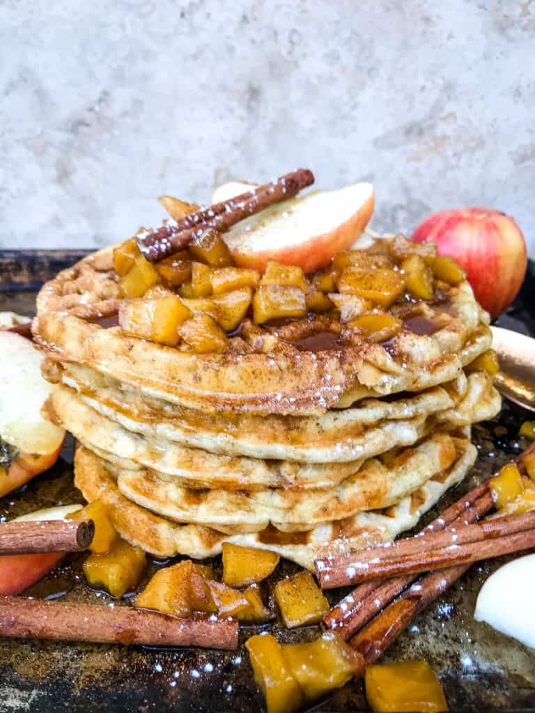 A stack of Cinnamon Apple Waffles with apple sauce
