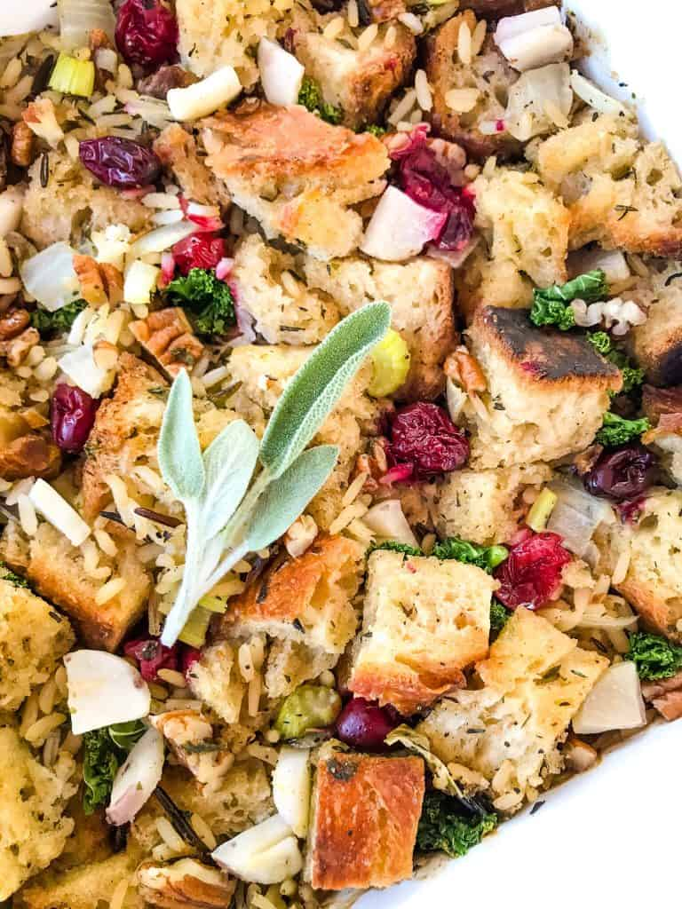 Close up of Thanksgiving Stuffing with Cranberries, Kale, Pecans, and Wild Rice in a white dish