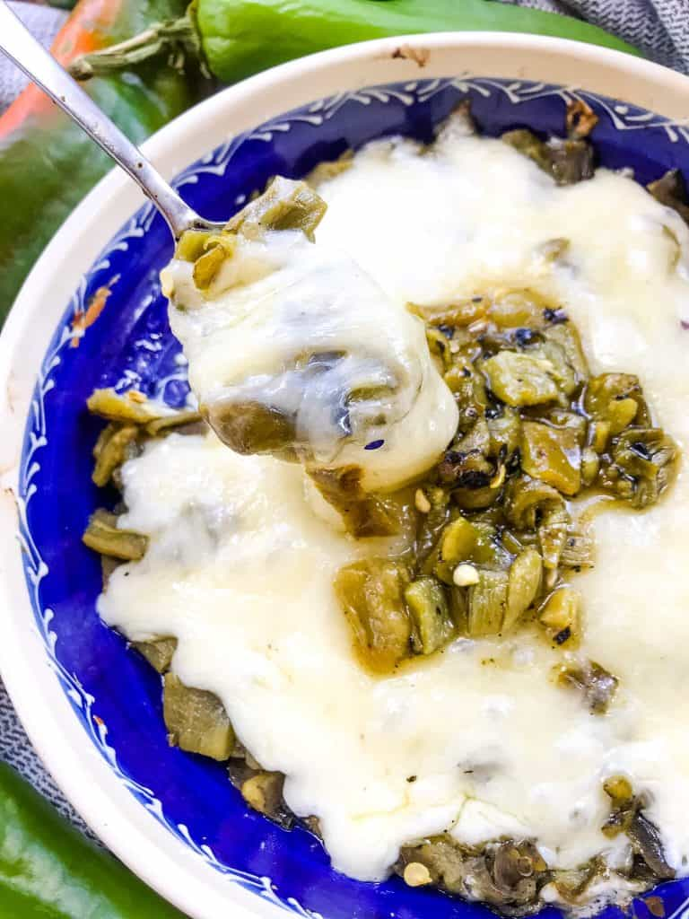 A spoon scooping out Hatch Green Chile Queso Fundido from a dish