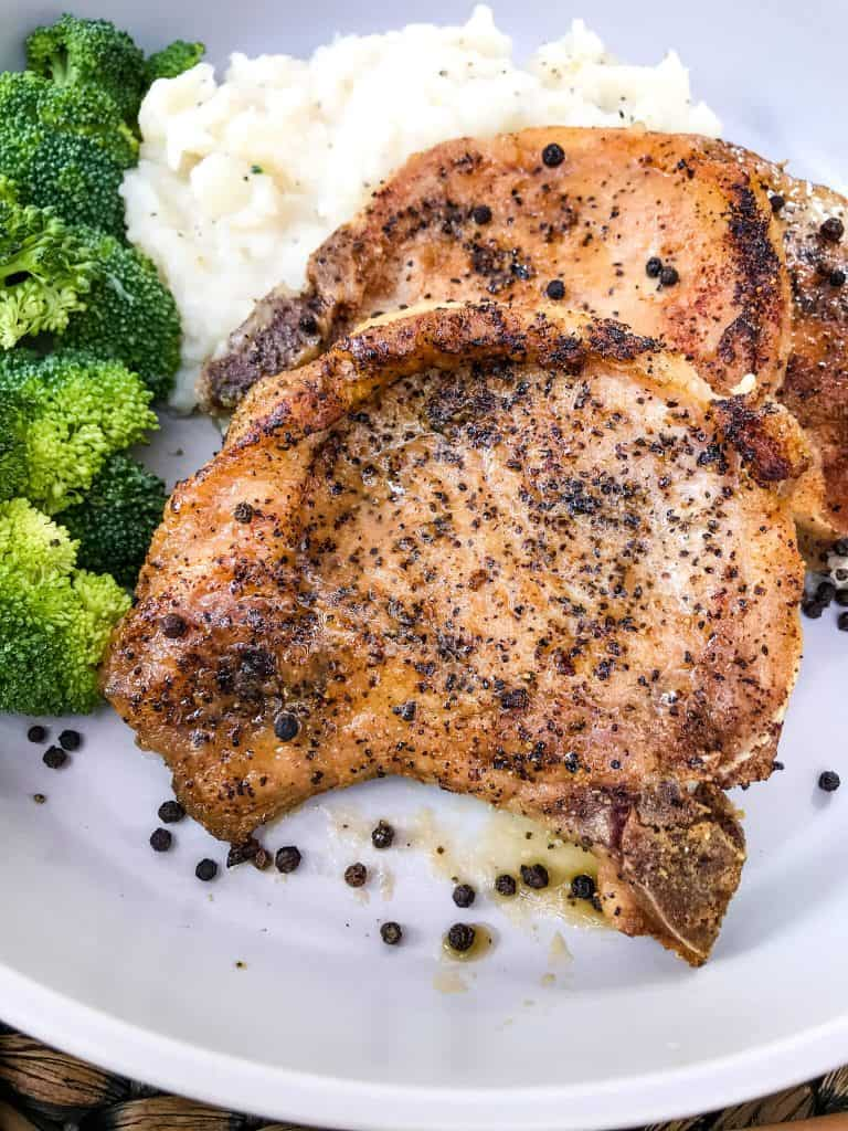 Peppercorn Garlic Pork Chops on a plate with broccoli and mashed potatoes