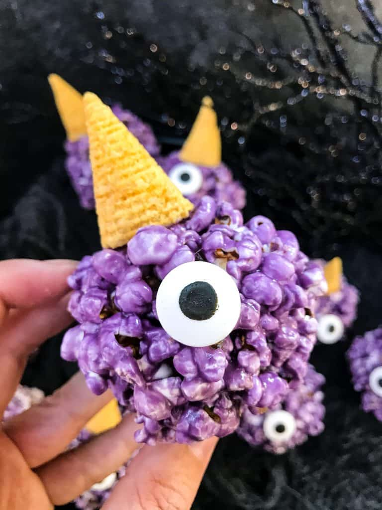 A hand holding a Purple People Eater Halloween Popcorn Ball