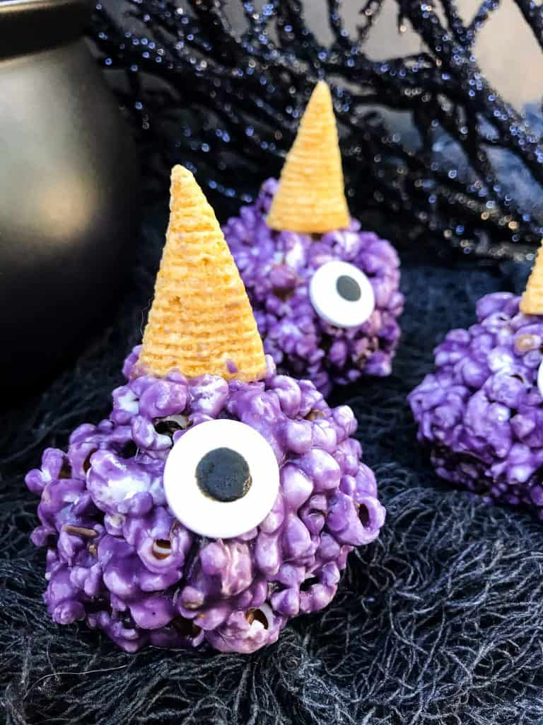 A purple popcorn ball with a horn and large eye sprinkle
