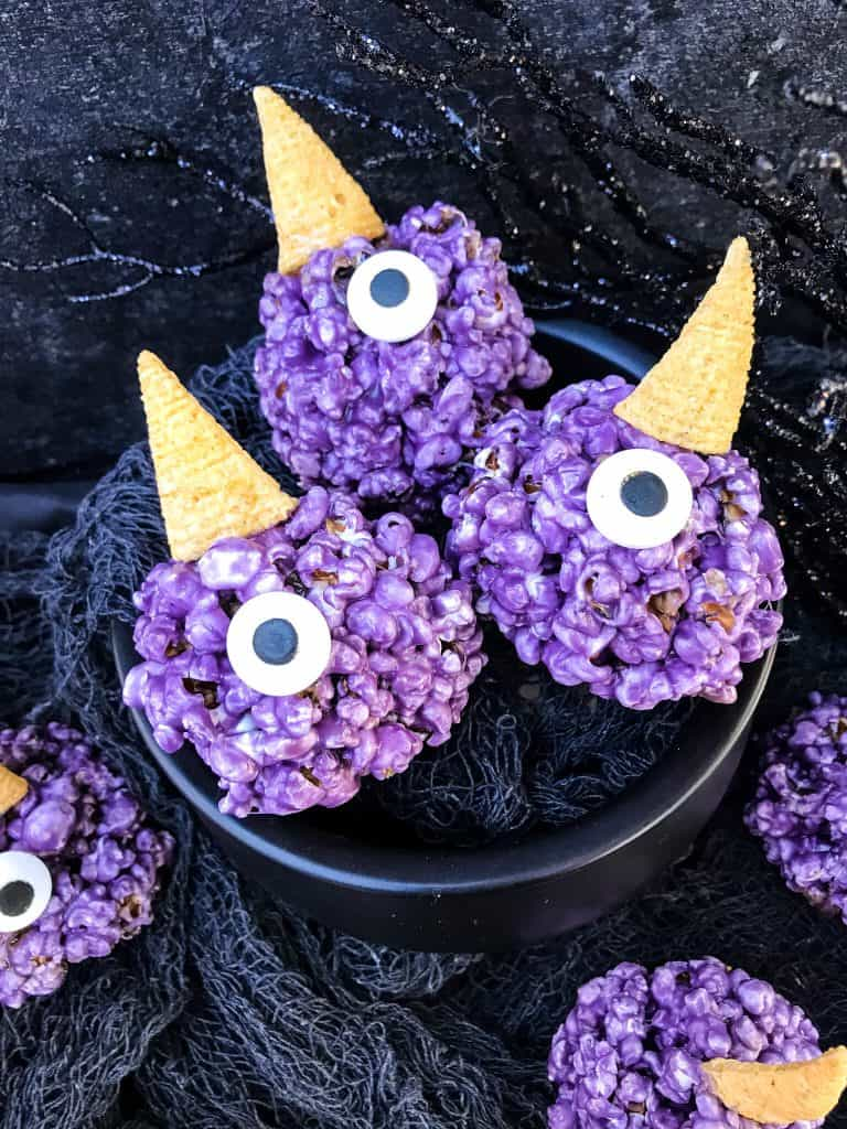 A cauldron with three Purple People Eater Halloween Popcorn Balls