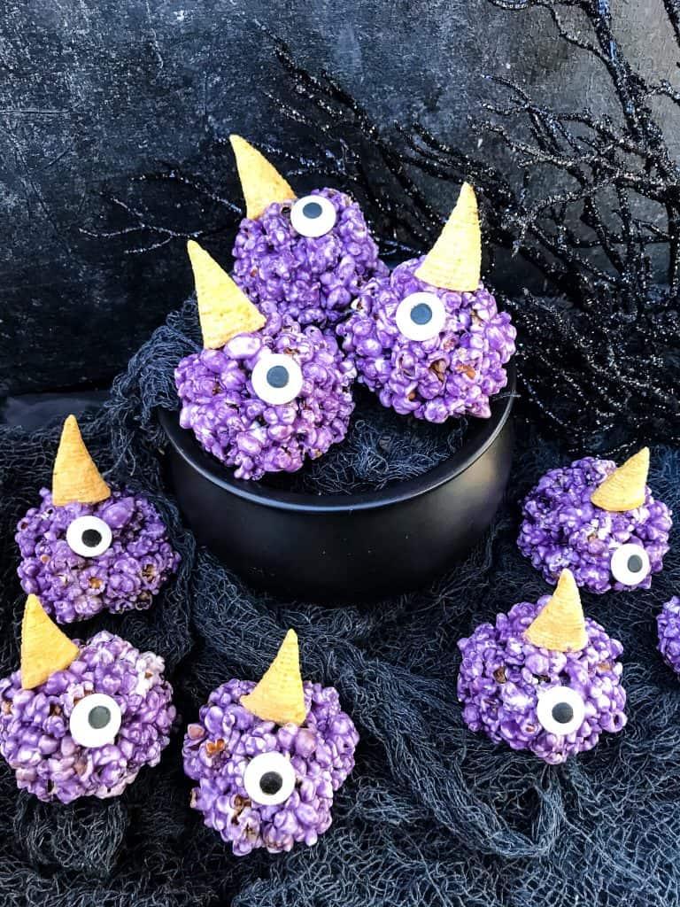 Purple People Eater Halloween Popcorn Balls in a cauldron and around it on gray gauze fabric