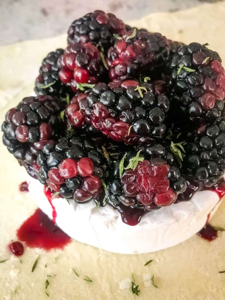 A brie wheel sitting on puff pastry, topped with jam and blackberries